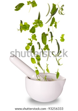 Herbs falling into mortar, isolated on white background - stock photo