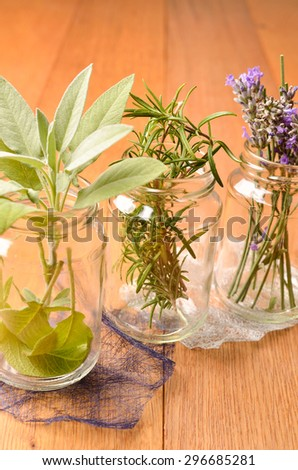 Herbs on a wooden table, rosemary lavender and sage in glasses - stock photo