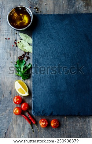 Herbs, spices, olive oil, salt, lemons and vegetables. Food background. Slate and wood background. Top view. - stock photo