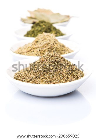 Herbs variety of rosemary, parsley, bay leaves and thyme in white bowl over white background