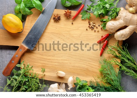 Herbs with a blank chopping board. Space for copy. - stock photo