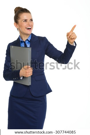 Here, a happy businesswoman holding a file under one arm, and pointing upwards with the other is happy as she points out her successes.