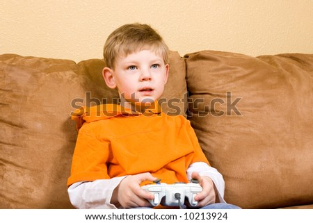 Here is a photo of a young boy sitting on a couch playing a video game.