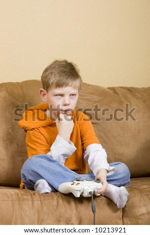 Here is a picture of a young boy playing a video game.