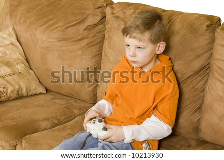 Here is a young boy sitting on a couch playing a video game