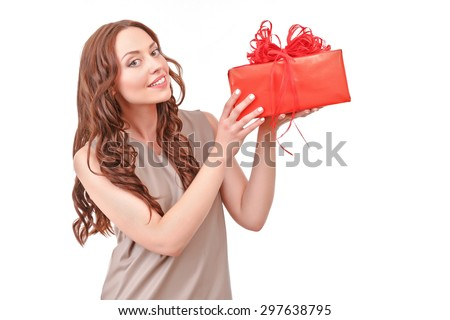 Here it is. Beautiful young-looking red-haired lady standing against isolated white background with big red present. - stock photo