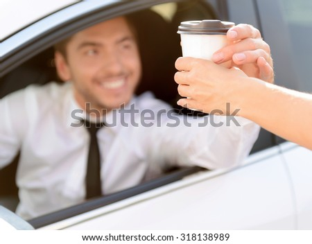 Here you are. Blissful handsome young businessman driving his car and getting coffee while evincing joy - stock photo