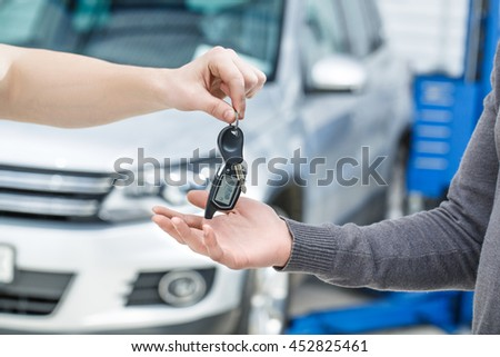 Here you go. Cropped closeup of a car mechanic passing the car keys to his client - stock photo