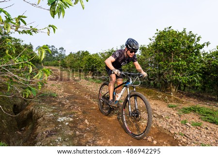Heredia, Costa Rica - May 08: Young man riding his mountain bike on rough roads true  coffee plantation. May 08 2016 Heredia, Costa Rica.