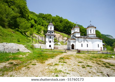 Hermitage or abbey in mountains, near a forest
