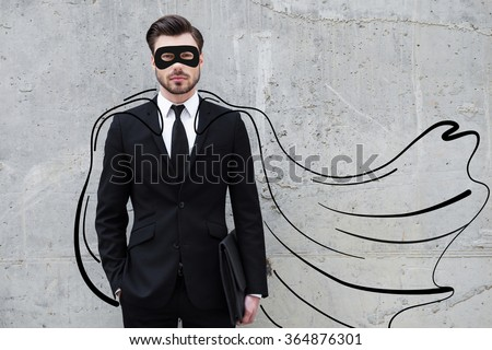 Hero in his business. Confident young businessman wearing a drawn cape and mask while standing against concrete wall - stock photo