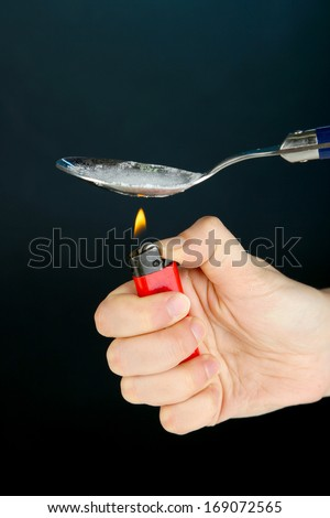 Heroin in spoon on black background - stock photo