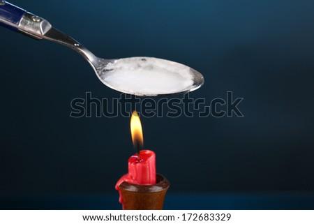 Heroin in spoon on dark blue background - stock photo