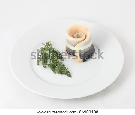 Herring and dill in white plate. - stock photo