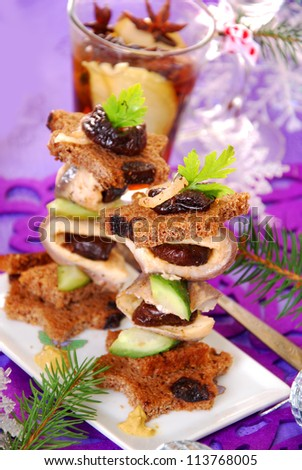 herring canapes with dark bread in star shape, prune and gherkin on christmas eve`s table - stock photo