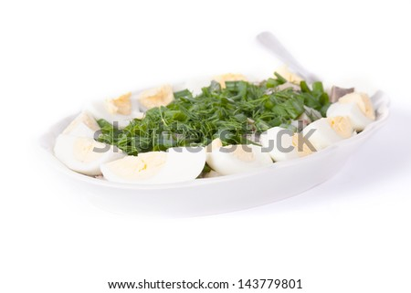 Herring, eggs and onion served on white plate