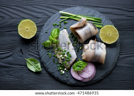 Herring fillet on a stone slate tray, black wooden background, top view
