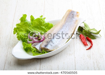 Herring fillet served onion and salad leaves