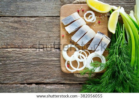 herring onion and herbs on wooden surface - stock photo