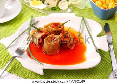 herring rolls in salsa sauce with saffron on fish shape plate for easter