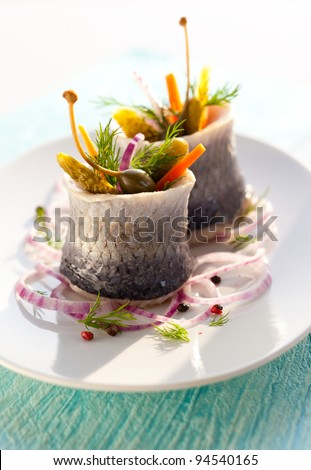 Herring rolls with pickled vegetables - stock photo