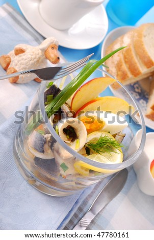 herring salad with egg and apple in glass bowl  for easter