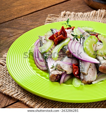 Herring salad with sun-dried tomatoes, celery and red onion on green plate - stock photo