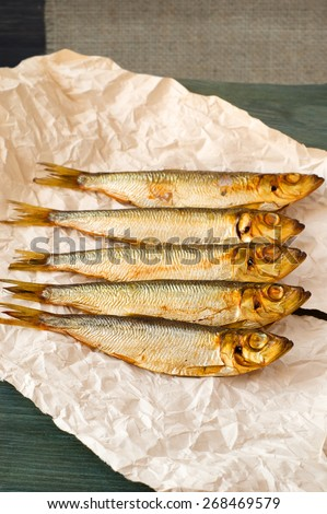 herring sprat fish smoked wooden table - stock photo