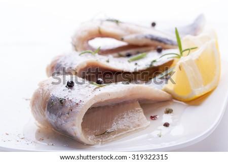 Herring with salt, pepper, herbs and lemon on white ceramic plate on white background  - stock photo