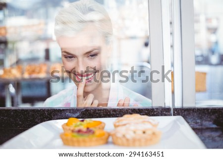 Hesitating pretty woman looking at fruit pie at the bakery - stock photo