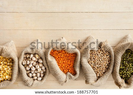hessian bags with cereal grains: peas, chick peas, red lentils, wheat and green mung on wooden table - stock photo