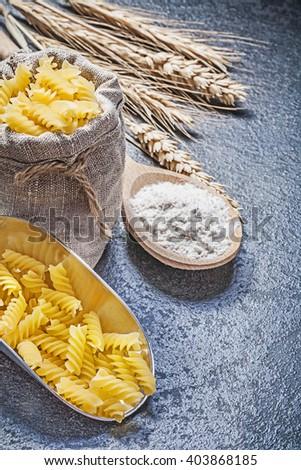 Hessian sack spiral macaroni serving scoop wooden spoon flour wheat rye ears on black background. - stock photo