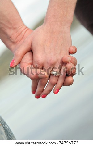 heterosexual couple holding hands showing engagement ring - stock photo