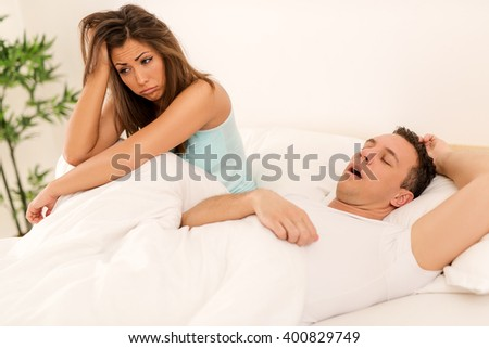 Heterosexual couple in bed, man sleeps and snoring with mouth open, while a tired woman irritated by snoring sitting on bed with head on arm. - stock photo