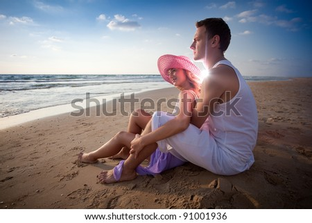 Heterosexual couple  on shoreline  looking  far away - stock photo