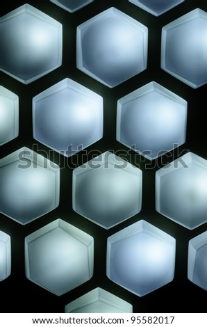 Hexagonal light fixtures in a pattern on dark wall