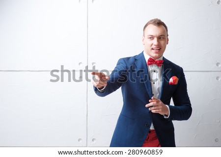 Hey, buddy! Happy young man in jacket and bowtie pointing away and expressing positivity while standing against white wall. - stock photo