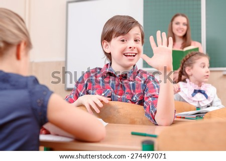 Hey everyone. Happy pupil boy waving with hand turned away from teacher in classroom. - stock photo