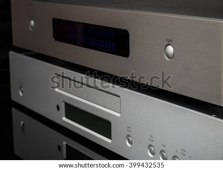 Hi-Fi stereo  musical system on black mirror table. CD player and digital to analog converter. - stock photo