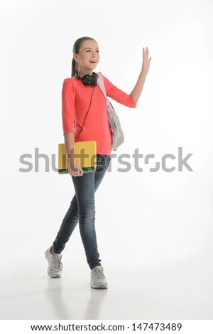 Hi guys! Happy teenage schoolgirl greeting someone while standing isolated on white - stock photo
