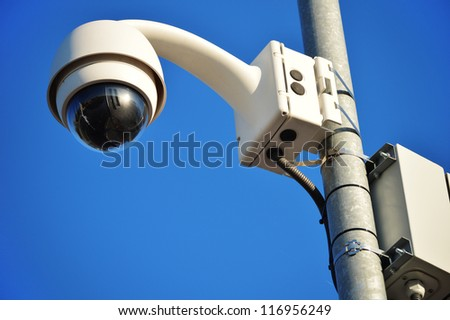Hi-tech dome type camera over a blue sky - stock photo