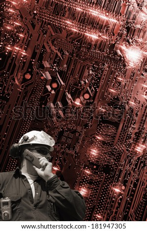 hi-tech engineer talking in phone with large circuit-board in the background - stock photo