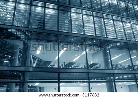 Hi-tech glass elevation of a modern office building at night with the lights turned on and the interior visible - office chairs and tables behind the windows - stock photo
