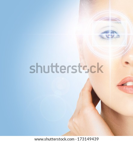 Hi-tech portrait of young and attractive woman with the holographic elements on her eyes (laser medicine and security concept) - stock photo