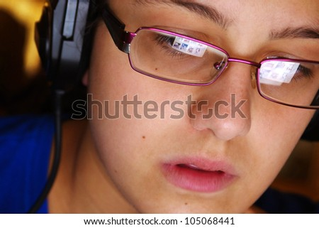 Hi-tech youth concept with a young girl using headphones and glasses reflecting her computer screen - stock photo