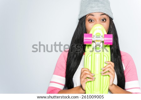 Hi there! Beautiful young African woman in funky clothes hiding behind her colorful skateboard while standing against grey background - stock photo