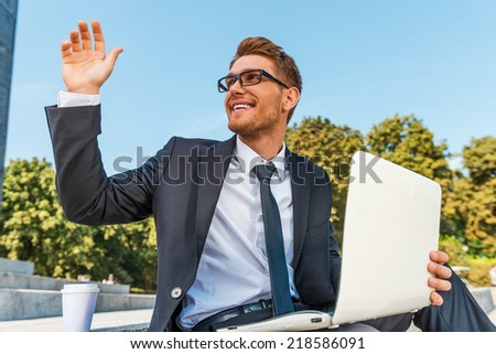 Hi there! Low angle view of cheerful young man in formalwear holding laptop and waving to someone while sitting outdoors - stock photo