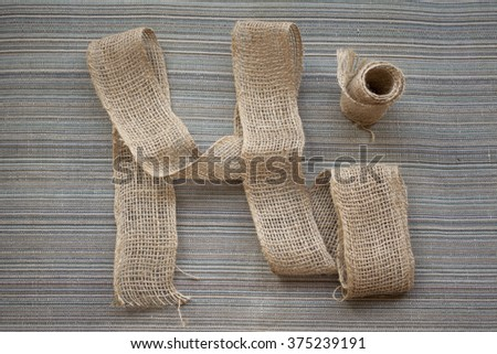Hi word made of sack cloth on striped texture background - stock photo