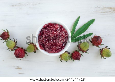 Hibiscus or roselle jam in a small cup on white table.  - stock photo
