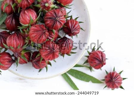 Hibiscus sabdariffa or roselle fruits in a plate on white wooden table.  - stock photo